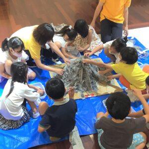 火山の土台作り!水のりで新聞紙ペタペタさせていきます