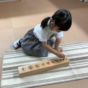 知育玩具の円柱さしをつかっています。穴の大きさに合わせて円柱をぴったりとさせるかな?